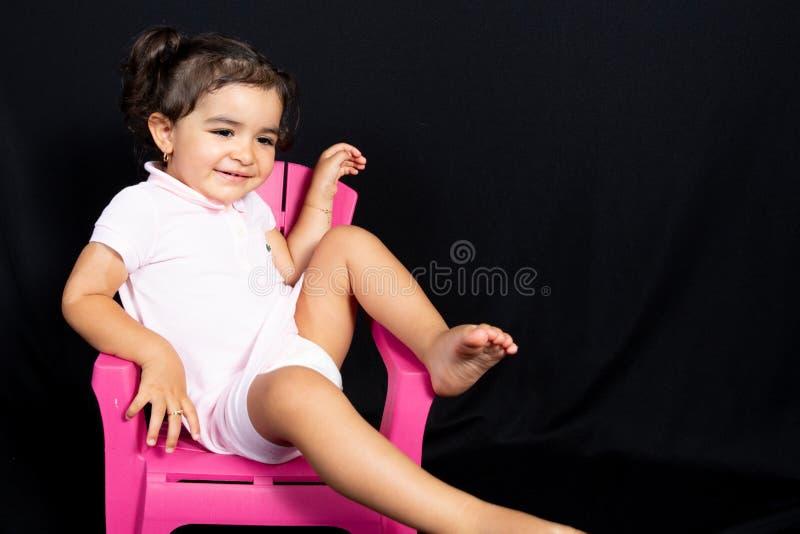 A criança da menina senta-se no sorriso feliz do divertimento da cadeira pequena do rosa no fundo preto fotografia de stock royalty free