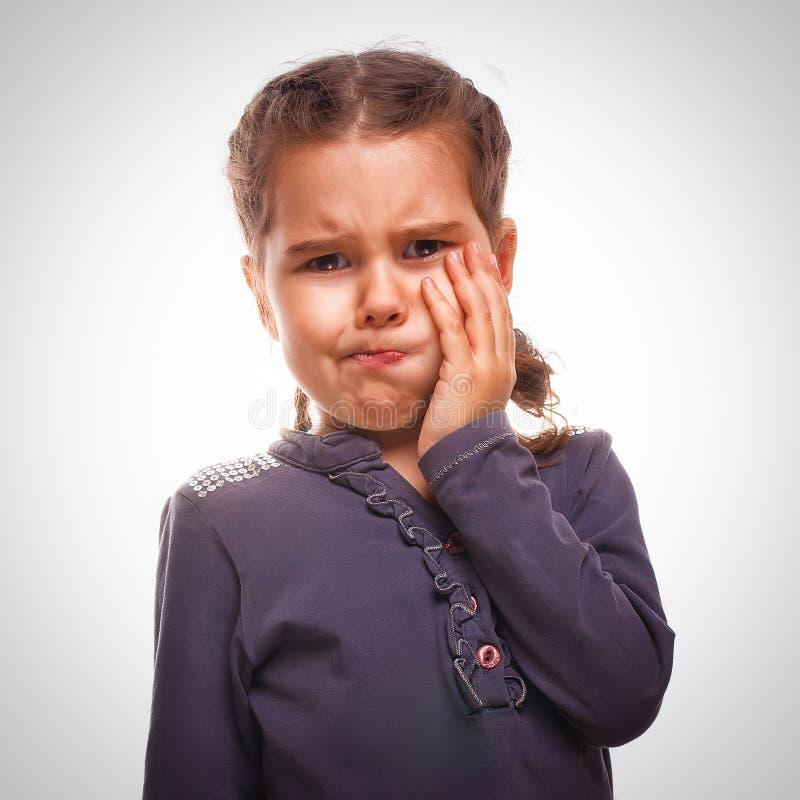 A criança da menina tem a dor de dente, dor de dente fotografia de stock