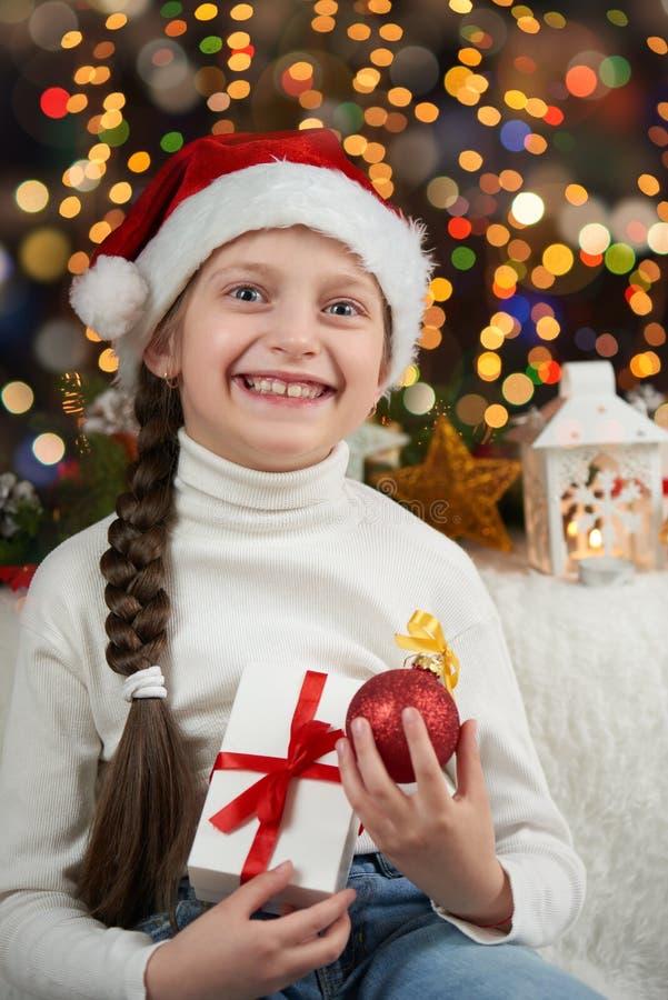 A criança da menina vestiu-se no chapéu de Santa com os presentes do Natal no fundo, no ano novo feliz e no conceito iluminados o imagens de stock