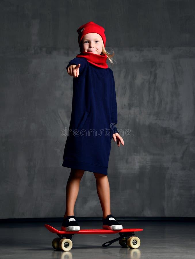 Criança da moça que está no skate no revestimento azul e no dedo apontando vermelho do lenço e o har foto de stock royalty free
