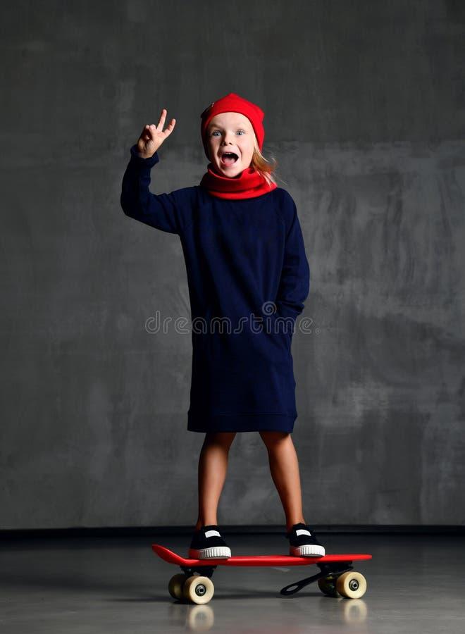 Criança da moça que está no skate no revestimento azul e no sinal mostrando vermelho do lenço e o har de paz que gritam imagens de stock royalty free