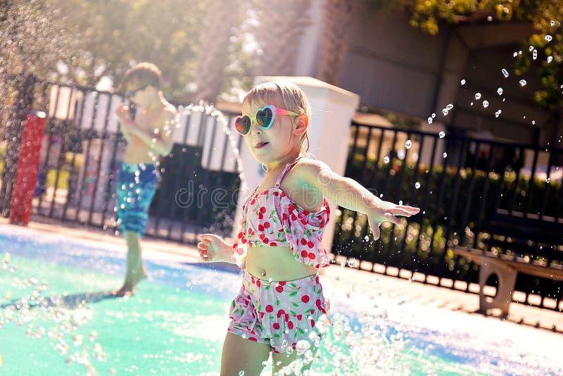 Criança da criança que corre através dos sistemas de extinção de incêndios da água no parque exterior do respingo fotos de stock