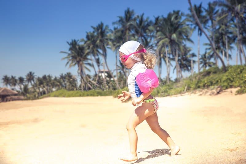 Criança da criança que corre no roupa de banho na praia com luz solar brilhante durante o estilo de vida feliz do curso da infânc fotos de stock
