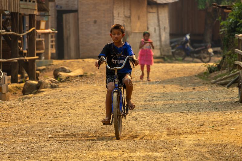 Criança da vila que biking Laos fotografia de stock royalty free