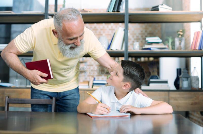Criança de ajuda da avó consciente com atribuição home imagens de stock