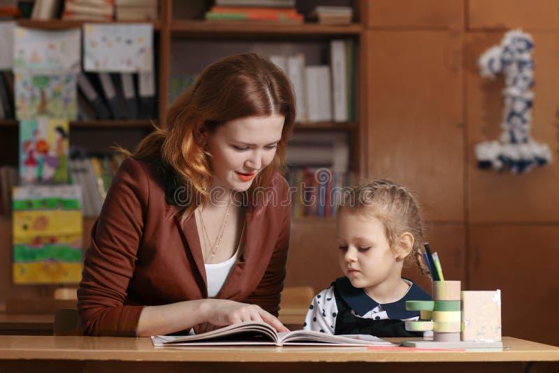 Criança de ajuda da mãe após a escola criança em idade pré-escolar que faz trabalhos de casa com ajuda do tutor conceito de ensin foto de stock