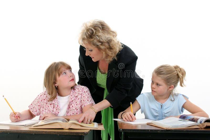 Criança de ajuda do professor na sala de aula fotografia de stock royalty free