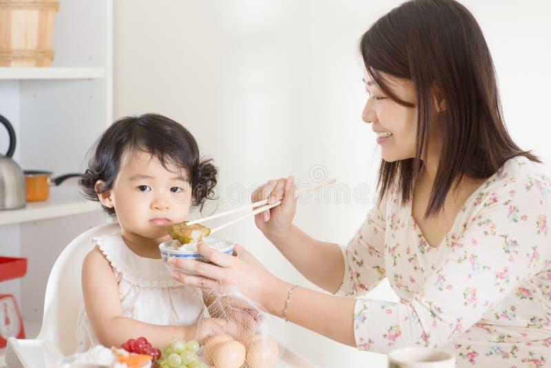 Criança de alimentação da mãe asiática fotografia de stock
