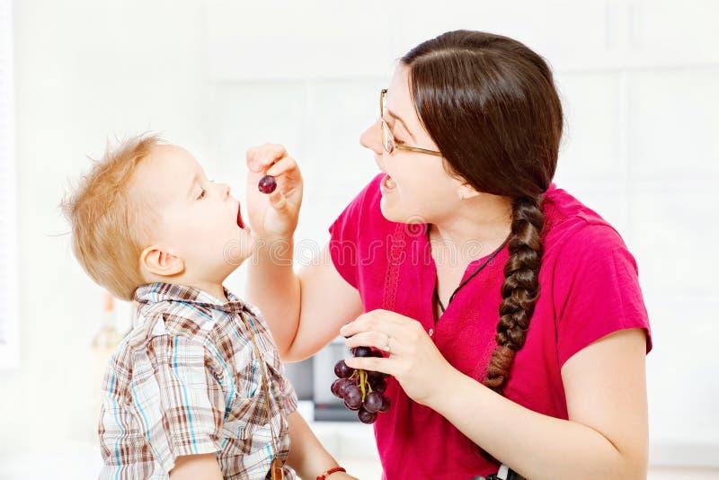 Criança de alimentação da mãe com uvas imagens de stock