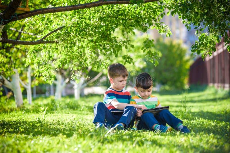 A criança de dois irmãos está encontrando-se na grama com tabuleta imagens de stock royalty free