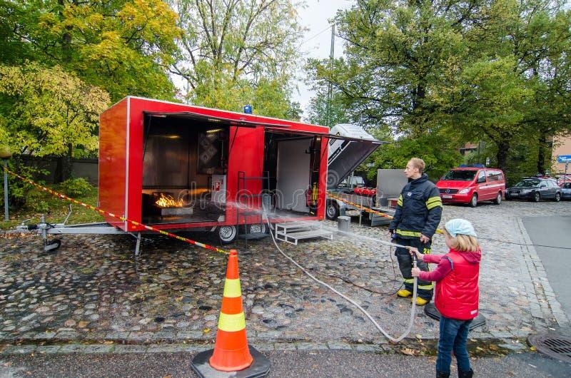 Criança de ensino do bombeiro para extinguir o fogo fotografia de stock royalty free
