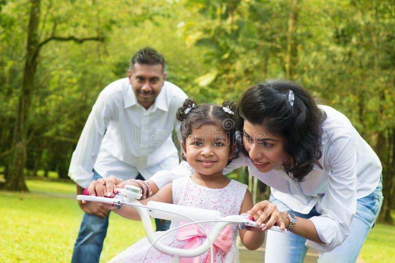 Criança de ensino do pai indiano para montar uma bicicleta fotografia de stock royalty free