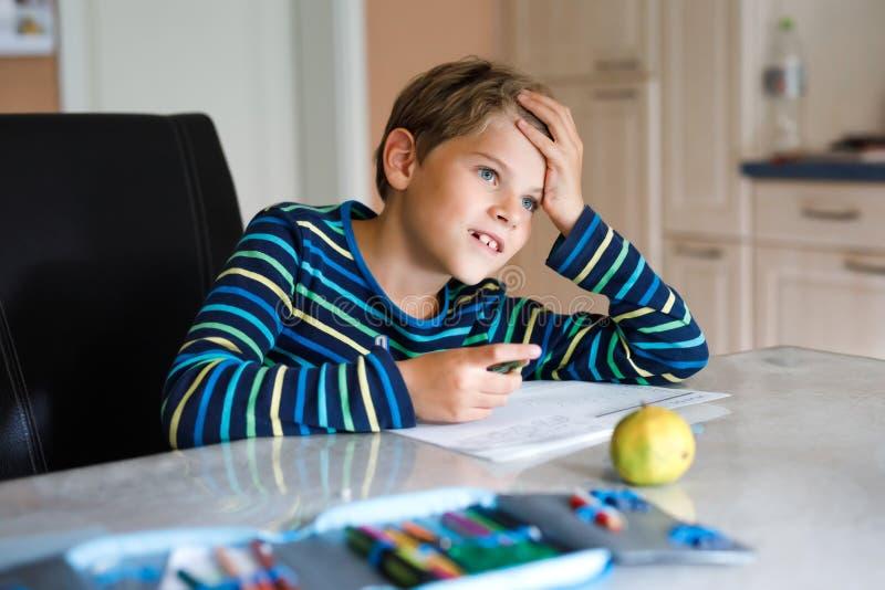 Criança de escola feliz, trabalhando duro, fazendo lição de casa durante o período de quarentena da doença pandêmica de corona Cr fotografia de stock royalty free