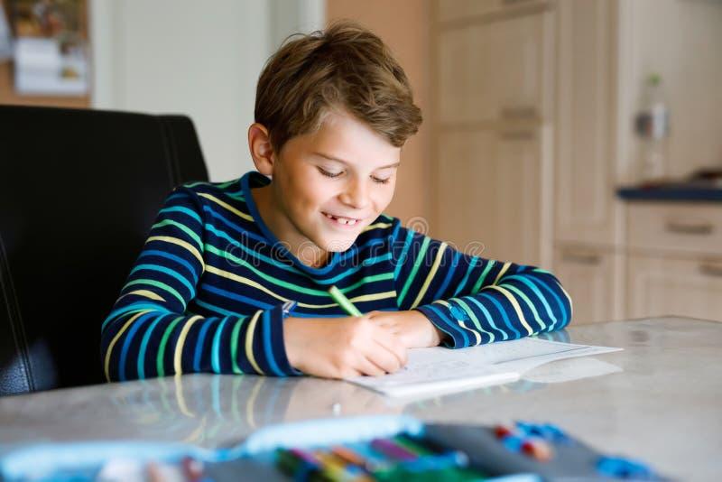 Criança de escola feliz, trabalhando duro, fazendo lição de casa durante o período de quarentena da doença pandêmica de corona Cr imagens de stock royalty free