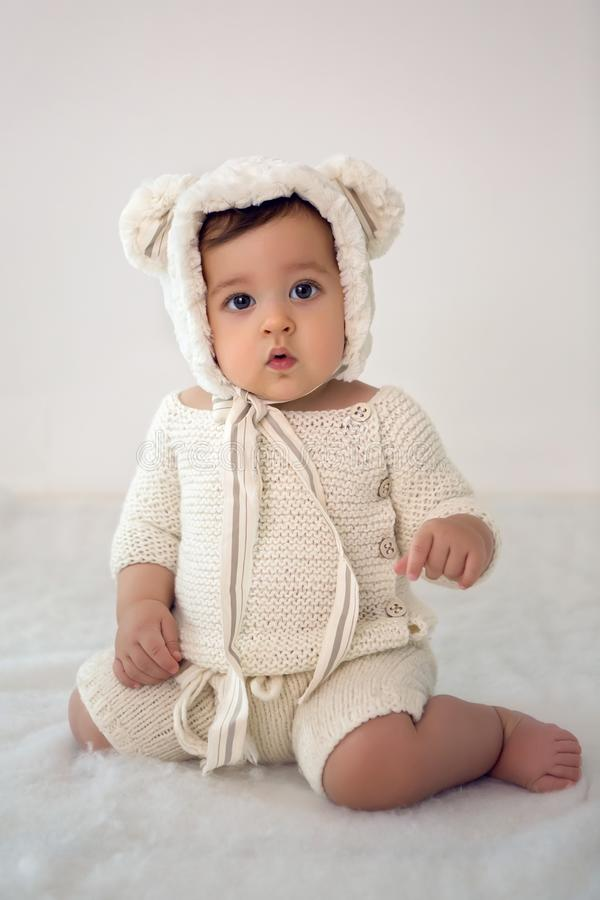 Criança de oito meses que sentam-se no estúdio em um chapéu fotografia de stock