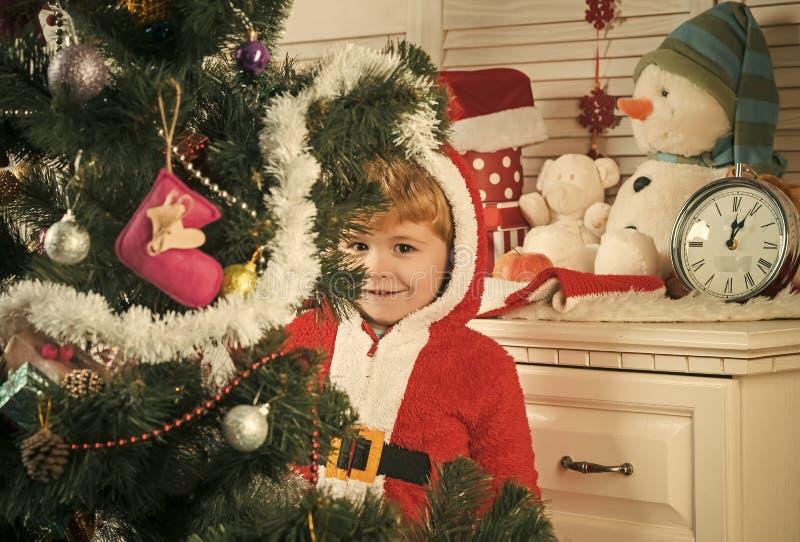 Criança de Papai Noel que decora a árvore de Natal imagem de stock royalty free