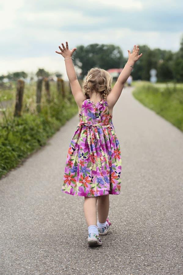 Criança de passeio com suas mãos acima no ar foto de stock