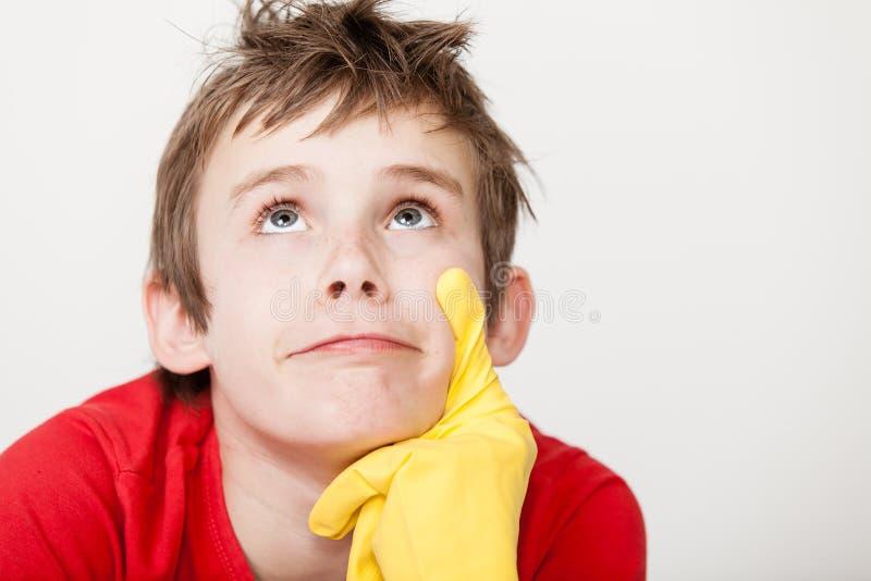 Criança de pensamento com o dedo gloved de borracha no queixo imagens de stock