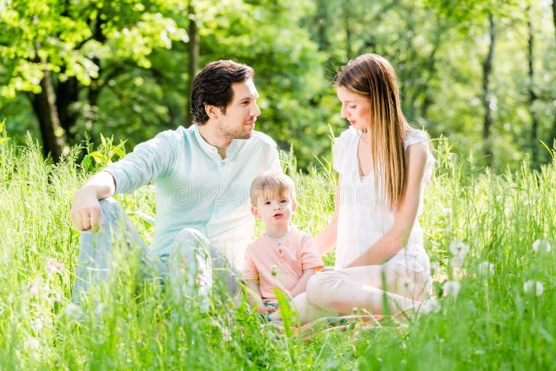 Criança de proteção da família que toma o filho no meio imagem de stock