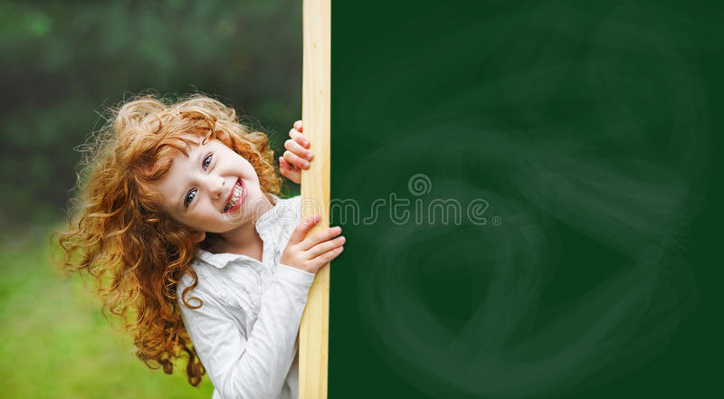 Criança de riso com o quadro-negro da escola que mostra Teet branco saudável fotos de stock