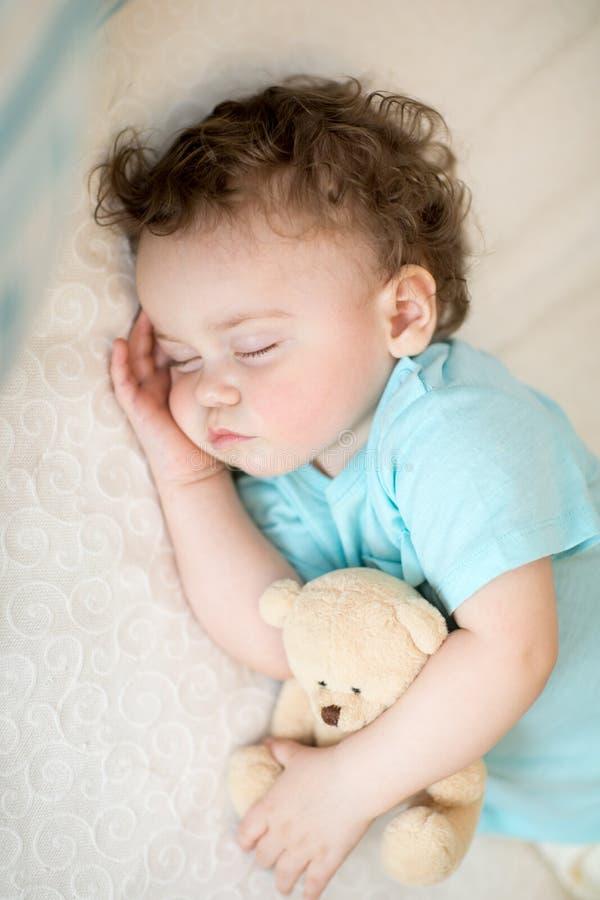 Criança de sono na cama, guardando um urso de peluche fotografia de stock