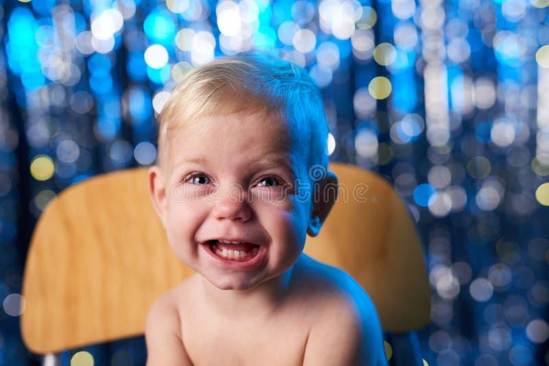 Criança de sorriso da criança sobre o fundo azul do bokeh dos feriados imagens de stock royalty free