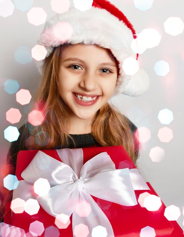 Criança de sorriso da menina do Natal no chapéu do ajudante do x-mas Santa com sorriso feliz da caixa de presente vermelha imagens de stock royalty free