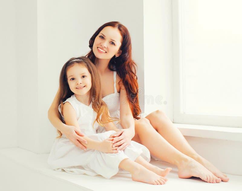 Criança de sorriso feliz da mãe e da filha junto em casa imagem de stock