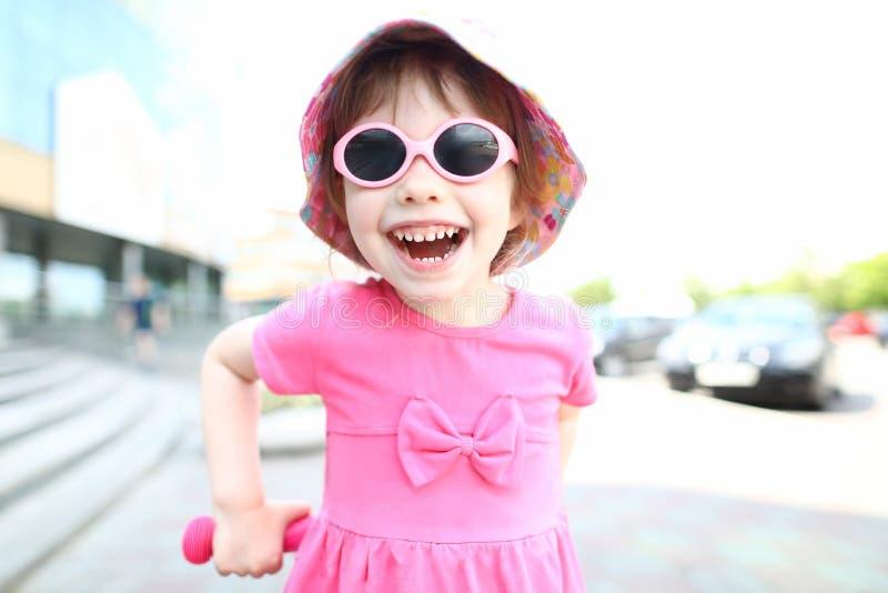 Criança de sorriso feliz da menina no retrato exterior dos óculos de sol imagens de stock royalty free