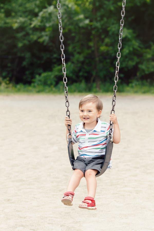 Criança de sorriso feliz do rapaz pequeno no short do tshirt e das calças de brim no balanço no campo de jogos do quintal fora fotos de stock royalty free