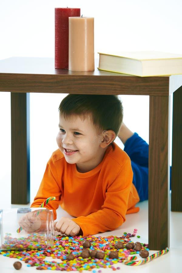 Criança de sorriso feliz que encontra-se sob a tabela com doces imagem de stock