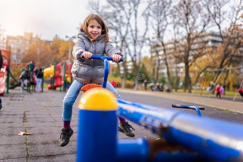 Criança de sorriso na balancê no campo de jogos no parque imagens de stock royalty free