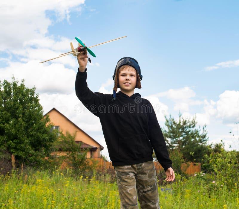 Criança de sorriso no capacete piloto com modelo plano fora sonho imagem de stock royalty free