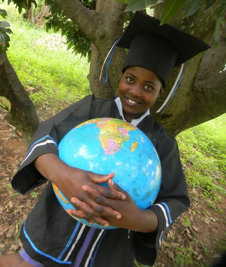Criança de sorriso no molho da graduação que guarda o mapa do globo do mundo fotografia de stock royalty free