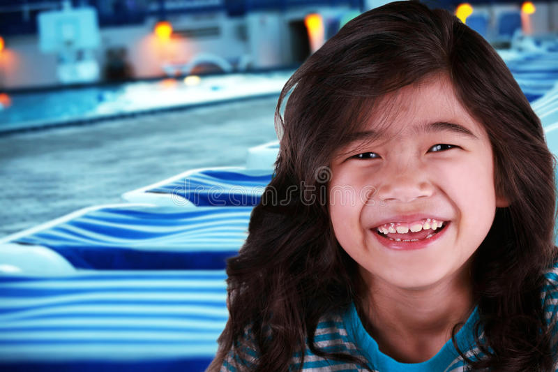 Criança de sorriso pelo poolside no crepúsculo fotografia de stock