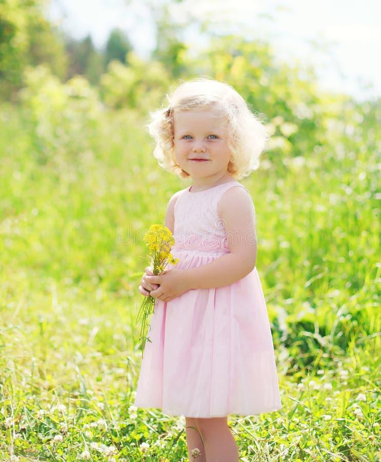 Criança de sorriso pequena da menina com as flores na mola fotos de stock