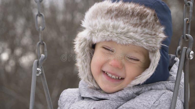 Criança de sorriso que balança no balanço Criança bonito do rapaz pequeno, bienal imagens de stock royalty free