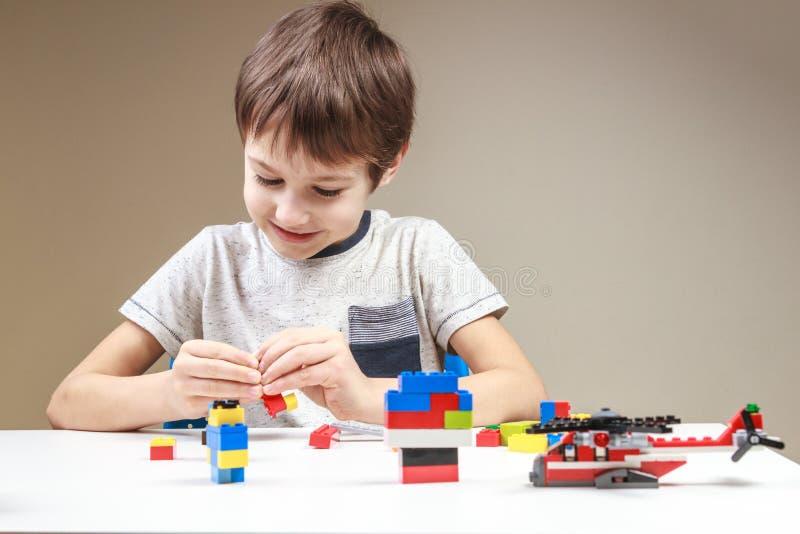 Criança de sorriso que joga com os tijolos plásticos coloridos da construção em casa imagens de stock royalty free