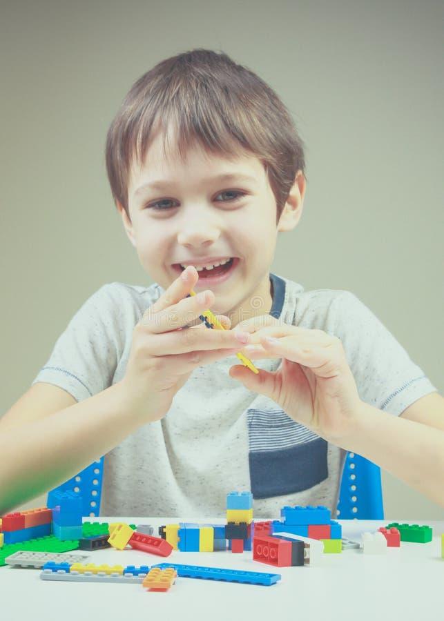 Criança de sorriso que joga com os tijolos plásticos coloridos da construção em casa fotografia de stock royalty free