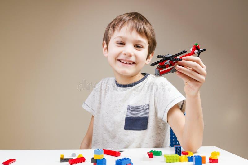 Criança de sorriso que joga com os tijolos plásticos coloridos da construção em casa fotos de stock royalty free