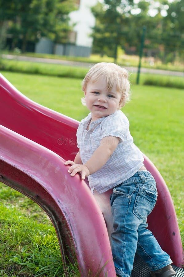 Criança de sorriso que joga em uma corrediça do bebê imagens de stock royalty free