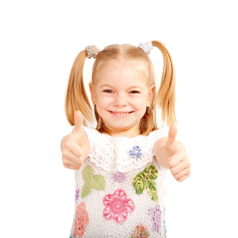 A criança de sorriso que mostra os polegares levanta o símbolo. fotos de stock
