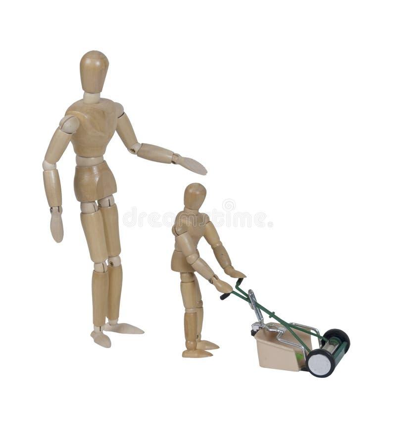Criança de supervisão adulta que usa o cortador de grama do estilo do impulso foto de stock