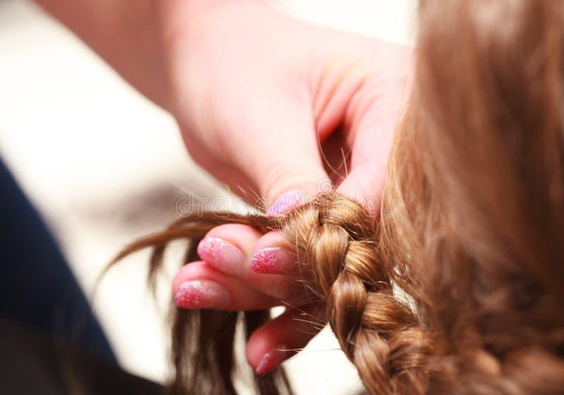 Criança de trança da menina do cabelo do cabeleireiro no salão de beleza do cabeleireiro imagem de stock royalty free