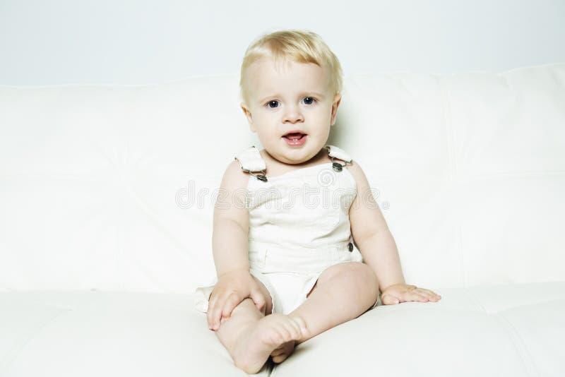 A criança de um ano aprende em um sofá fotos de stock royalty free