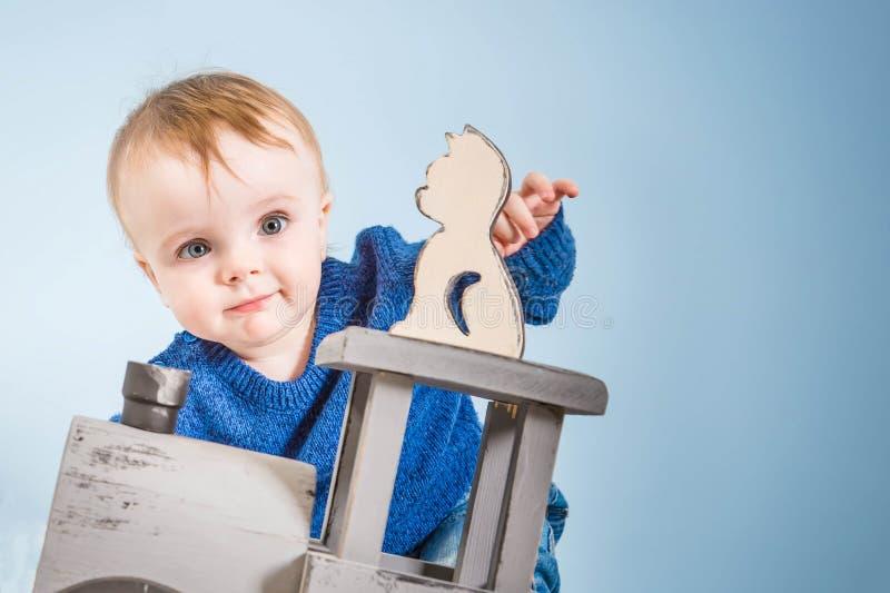 A criança de um ano feliz em uma camiseta azul joga brinquedos de madeira Bebê louro no fundo azul Gato e trem da madeira imagem de stock