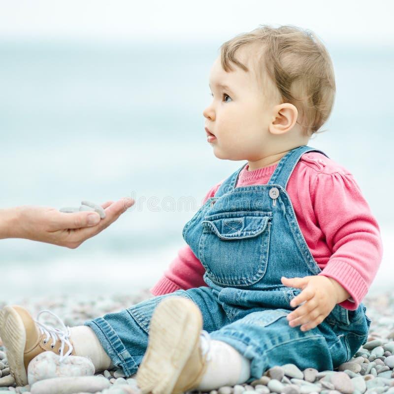 Criança de um ano na praia na mola fotografia de stock royalty free