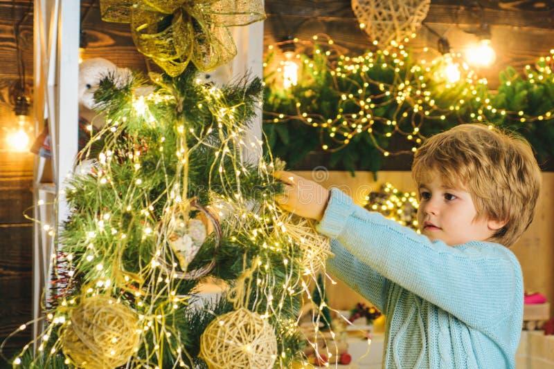 Criança decorando árvore de Natal com bauble decorações de Natal Retrato de Santa Criança com bauble olhando para a câmera fotografia de stock