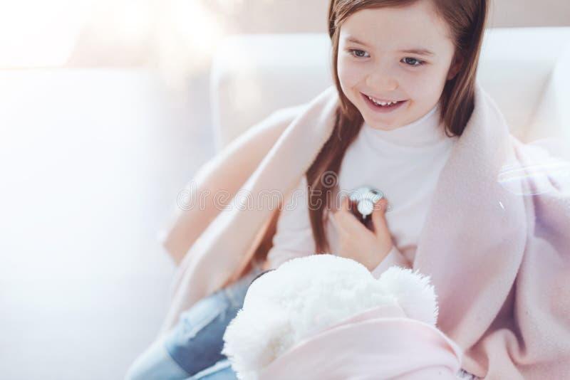 Criança deleitada positiva que joga com seu urso imagem de stock