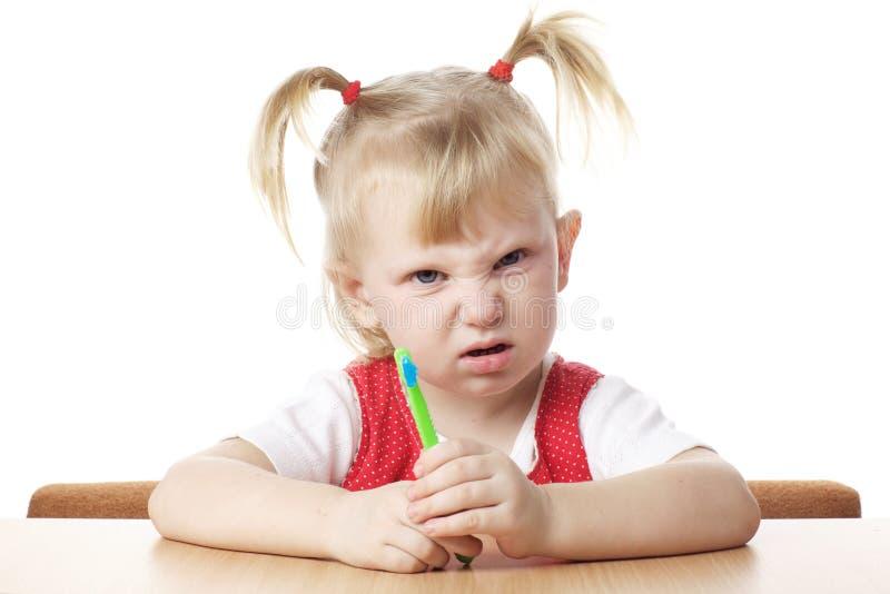Criança desagradada com toothbrush imagem de stock royalty free